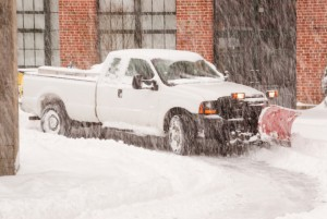 pick-up truck with snowplow attached working the street during a blizzard.